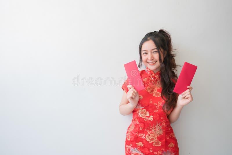 Femmes asiatiques dans des robes et la représentation de cheongsam de chinois traditionnel des enveloppes rouges pendant la nouve photographie stock libre de droits