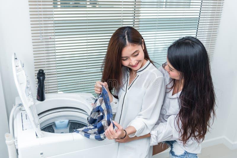 Femmes asiatiques de couples faisant les travaux domestiques et des corvées devant la machine à laver et chargeant des vêtements  image stock