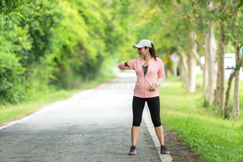 Femmes asiatiques de coureur pulsant pour le soin sain photo stock