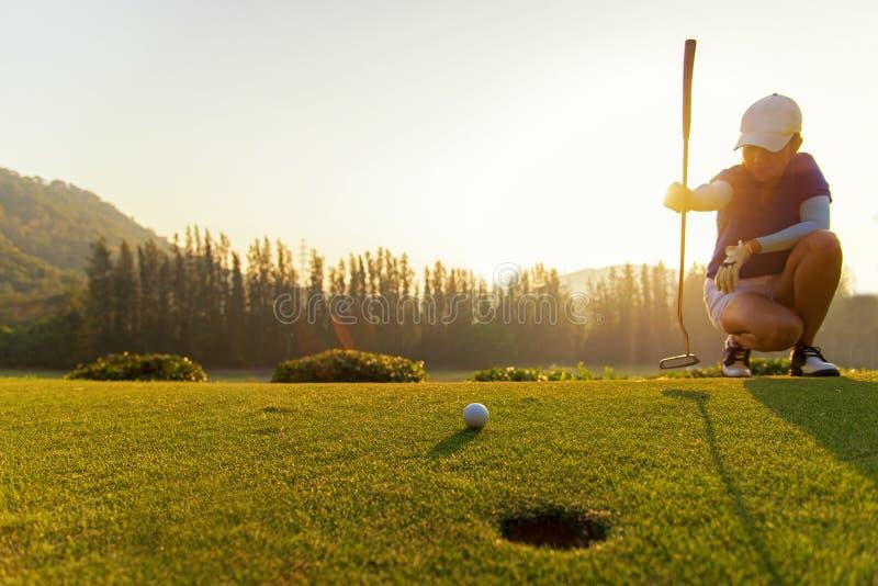 Femmes asiatiques de Gofer mettant la boule de golf images stock