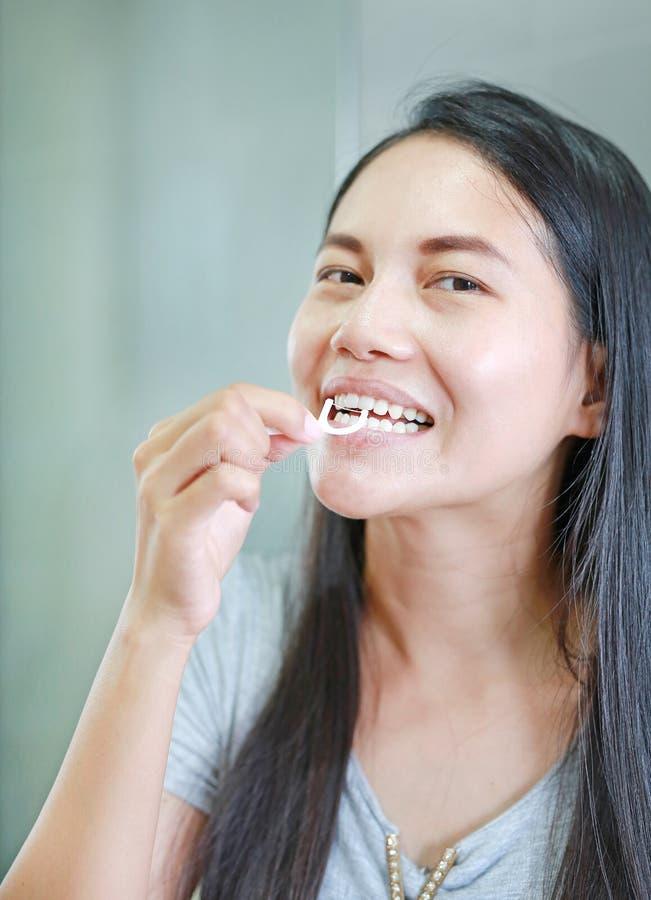 Femmes asiatiques de sourire employant le fil dentaire pour les dents saines photos stock