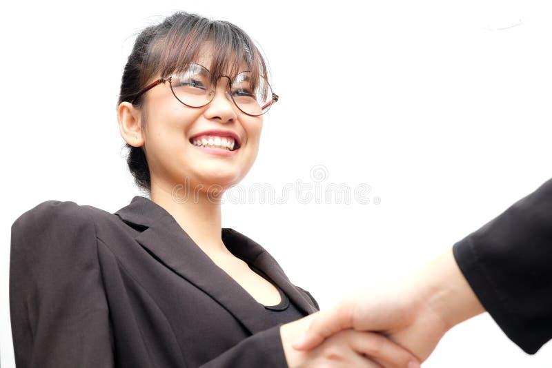 Femmes asiatiques de sourire en verre d'affaires serrant la main avec la personne image stock