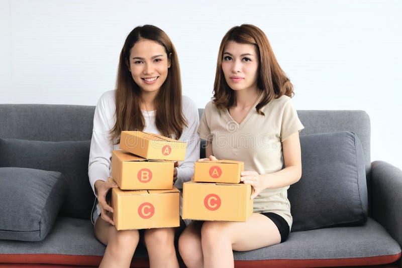 Femmes asiatiques gaies de propriétaire d'entrepreneur avec la boîte en carton se reposant sur le sofa moderne à la maison En lig photo stock