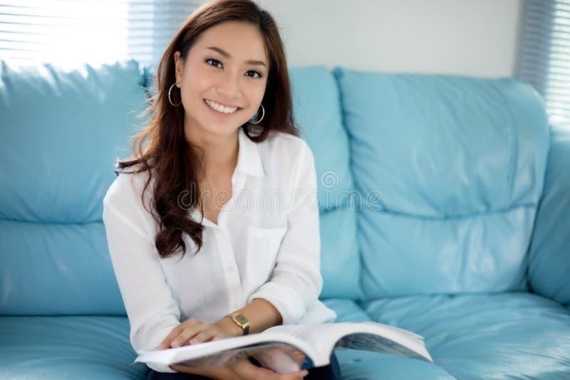 Femmes asiatiques souriant et lisant un livre pour la relaxation à la maison image stock