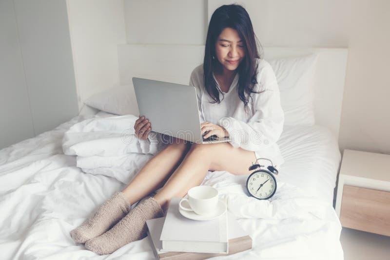 Femmes asiatiques sur le lit blanc La lecture de femmes se r?veillent et en travaillant au livre d'ordinateur portable et de lect photo libre de droits