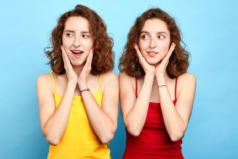 Femmes astucieuses adroites avec des paumes sur leurs mentons regardant loin photo stock