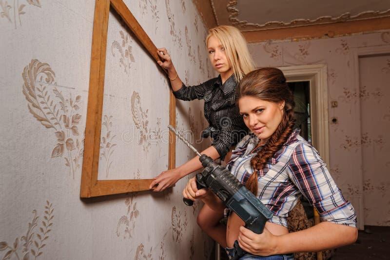 Femmes attirantes avec le perforateur et le cadre images libres de droits