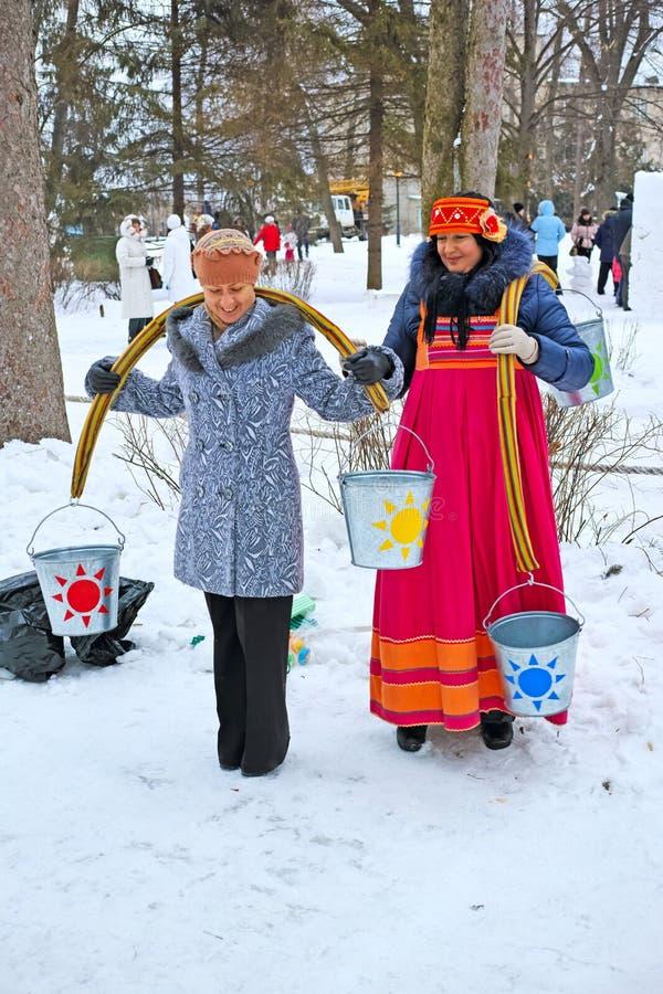 Femmes avec des balanciers portant des seaux de l'eau image stock