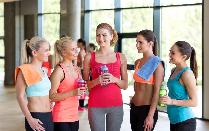 Femmes avec des bouteilles de l'eau dans le gymnase image stock