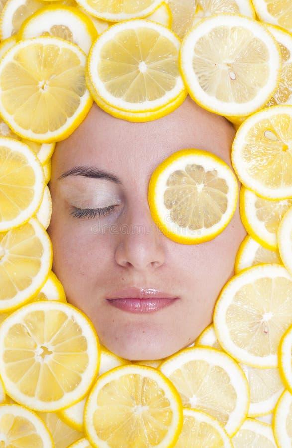 Femmes avec des citrons sur le visage images libres de droits