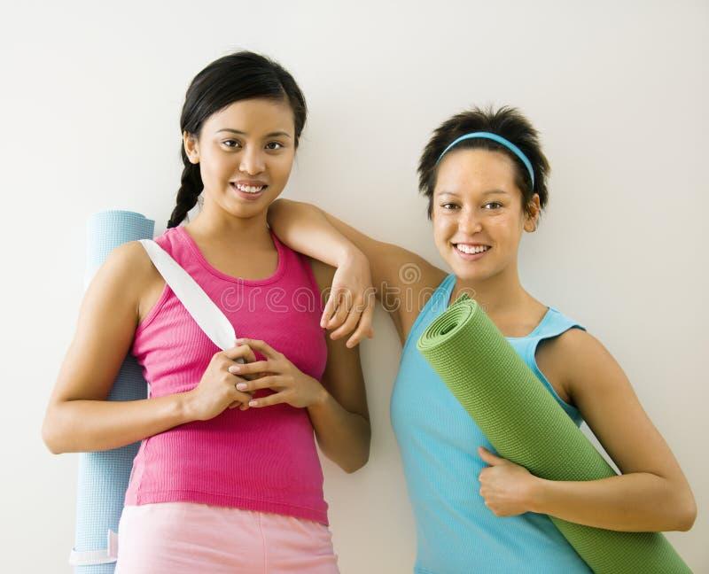 Femmes avec des couvre-tapis de yoga photos stock