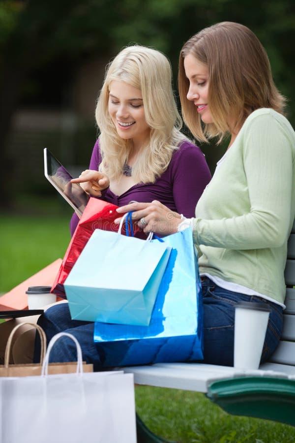 Femmes avec des paniers utilisant la tablette dehors photo libre de droits