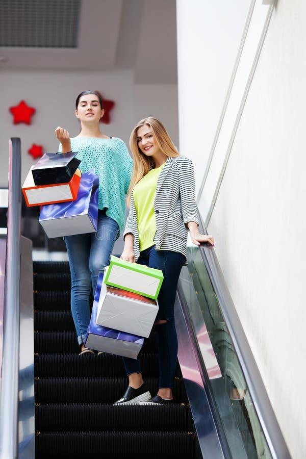 Femmes avec des sacs sur l'escalier mobile photo stock