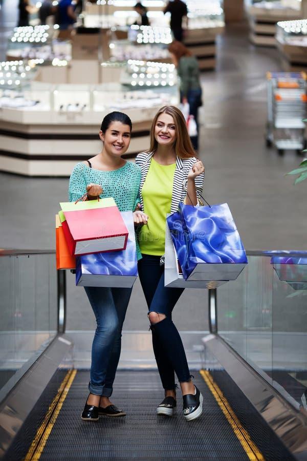 Femmes avec des sacs sur l'escalier mobile photographie stock libre de droits