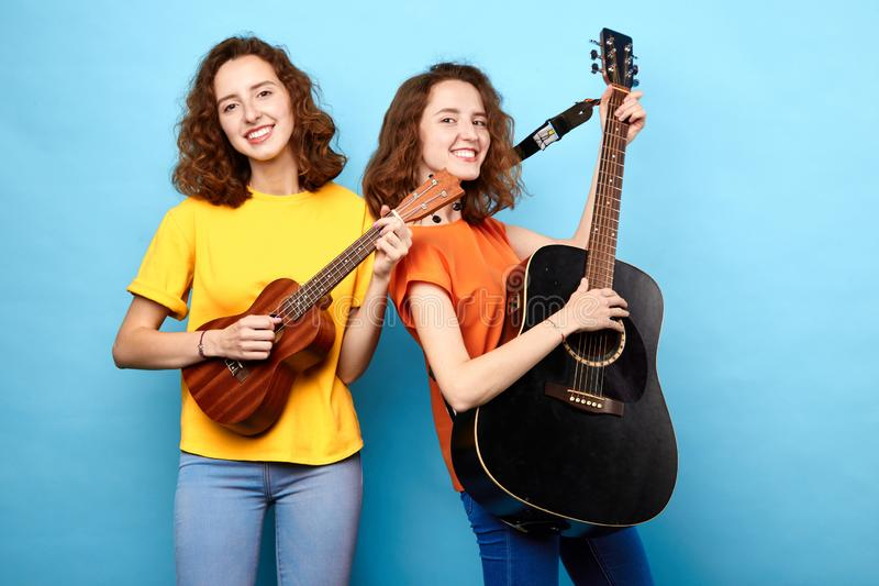 Femmes avec du charme douées appréciant jouant la guitare photo libre de droits