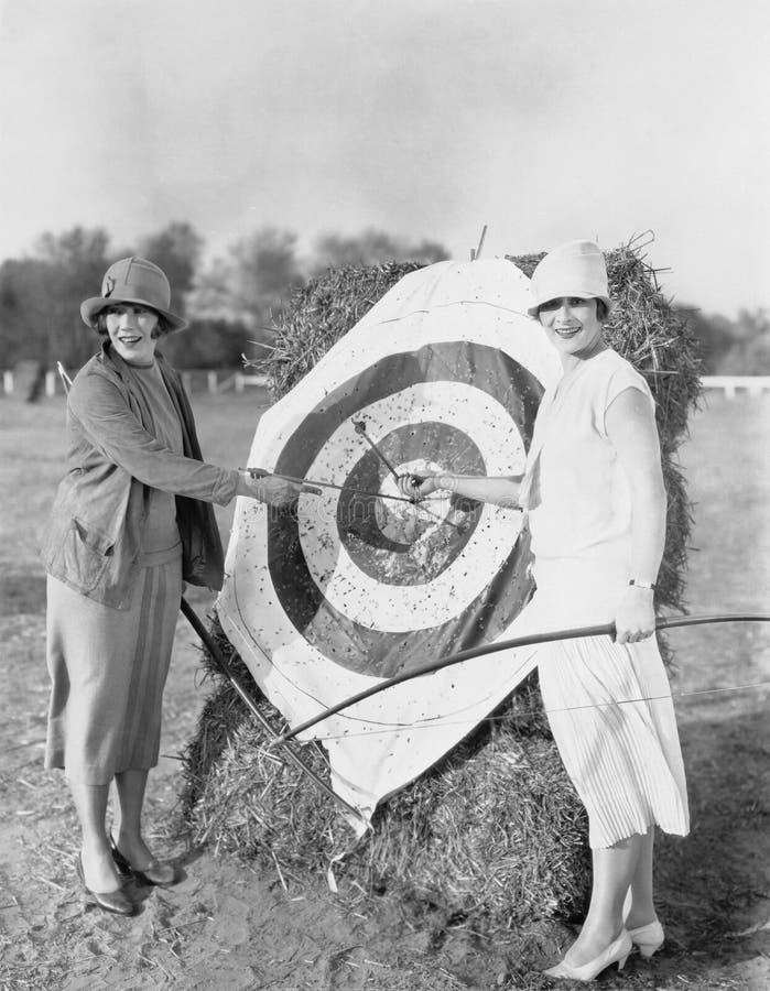 Femmes avec l'oeil de taureaux dans la cible de tir à l'arc (toutes les personnes représentées ne sont pas plus long vivantes et  images libres de droits