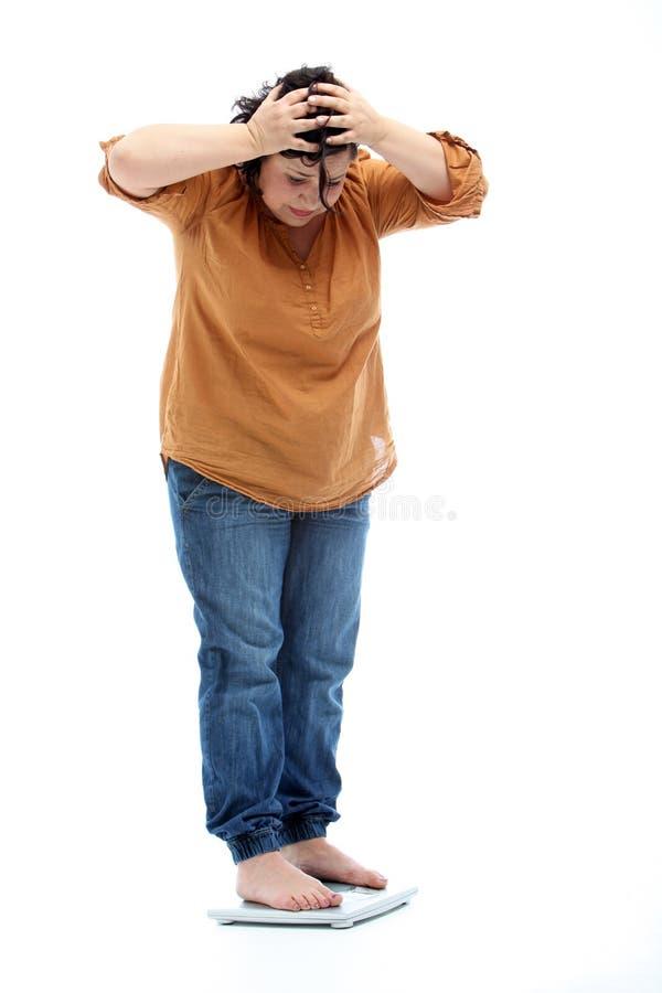 Femmes avec la position de poids excessif sur une échelle photos stock