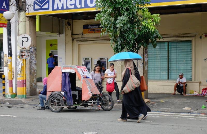 Femmes avec le parapluie marchant sur la rue dans Chinatown, Manille image stock