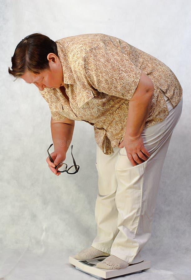 Femmes avec le poids excessif par derrière sur des échelles photo stock