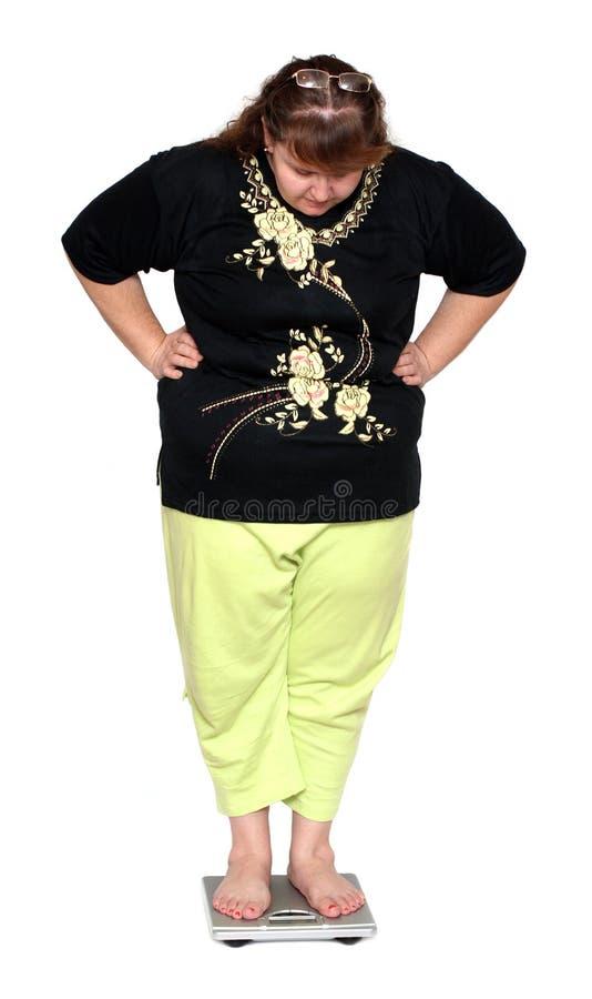 Femmes avec le regard de poids excessif sur des échelles image stock
