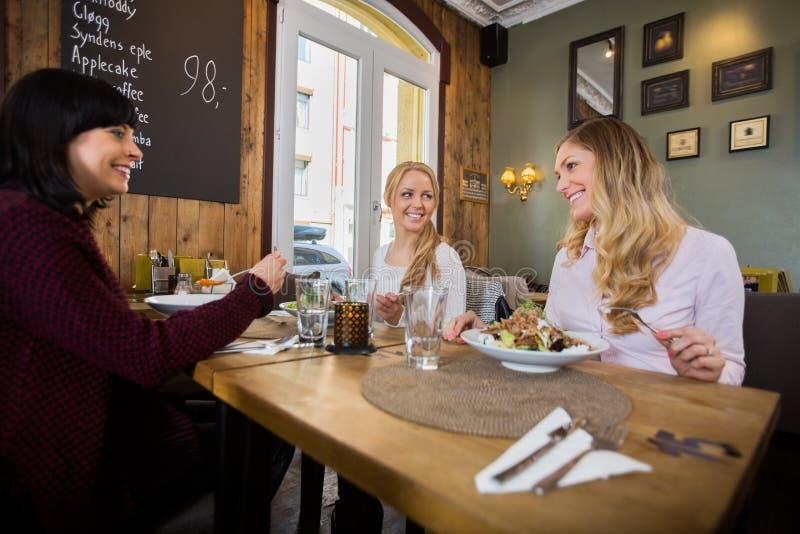 Femmes ayant la nourriture dans le restaurant photographie stock