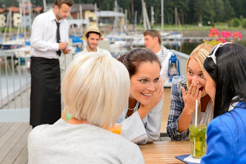 Femmes de bavardage s'asseyant à la barre de port photographie stock