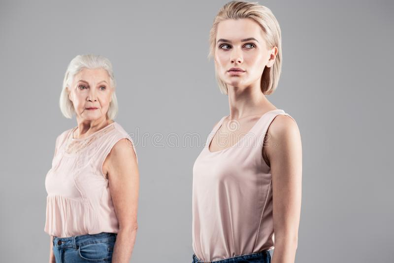 Femmes belles sérieuses utilisant les mêmes équipements et faisant les mêmes mouvements photographie stock