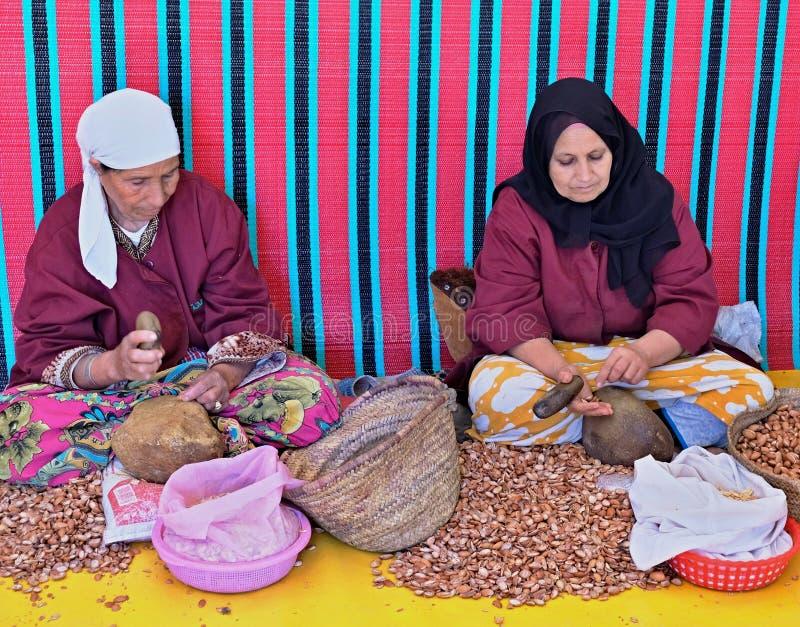 Femmes cassant des écrous et extrayant des écrous d'argan à un pétrole, aux cosmétiques et à l'usine de médecine faite à partir d photographie stock