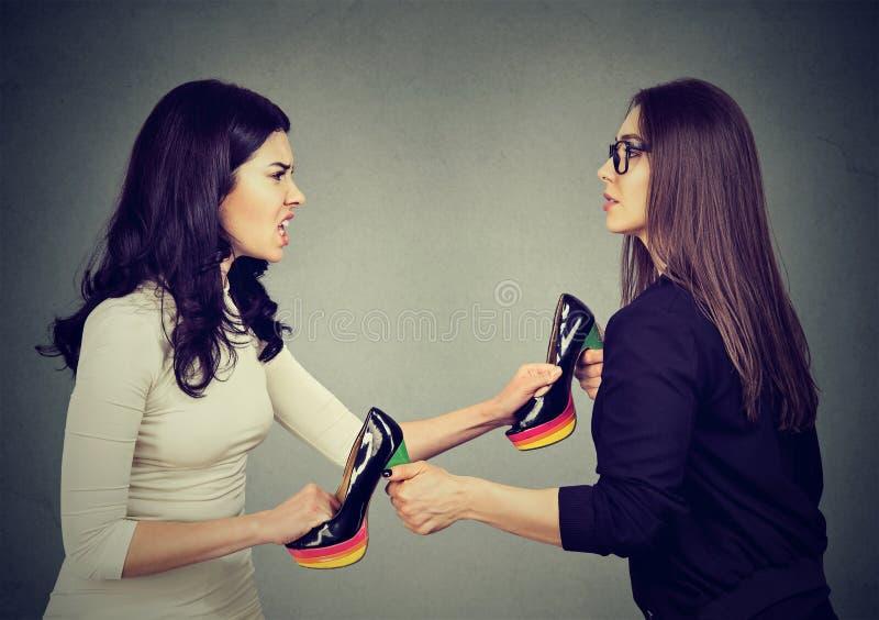Femmes combattant le déchirement tirant les chaussures distantes images stock