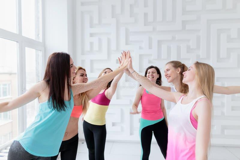 Femmes convenables sportives utilisant des vêtements de sport donnant à cinq photos stock