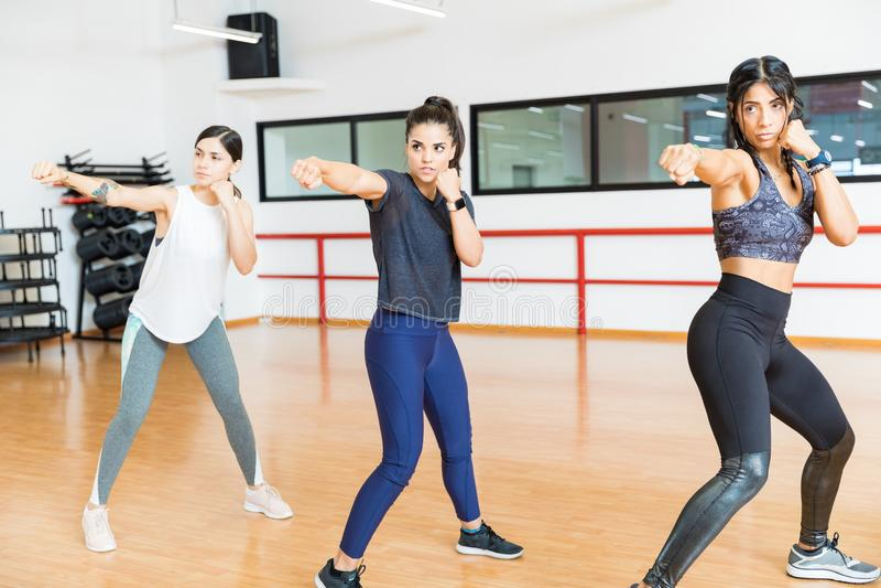 Femmes déterminées poinçonnant l'air dans le gymnase images stock
