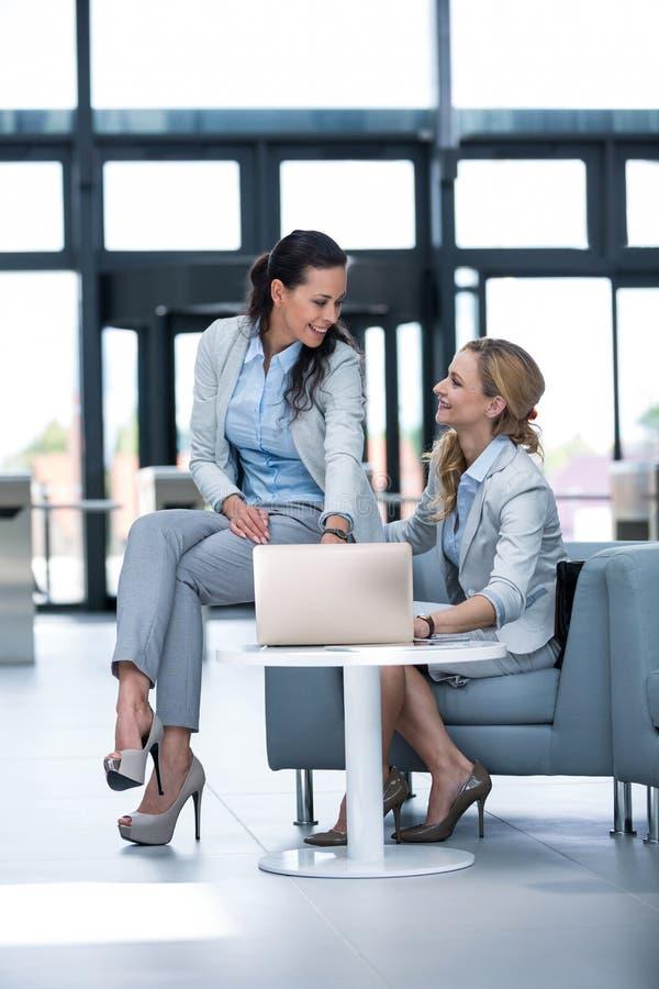 Femmes d'affaires à l'aide de l'ordinateur portable et ayant une discussion photos stock