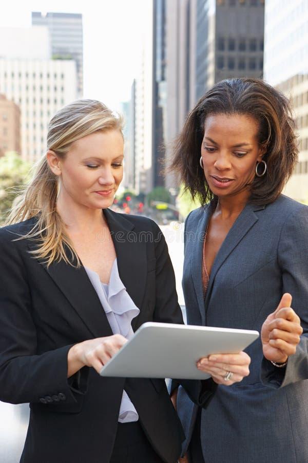 Femmes d'affaires à l'aide du comprimé de Digital en dehors du bureau photo stock