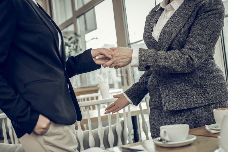 Femmes d'affaires élégantes réussies serrant leur main après négociation photos stock