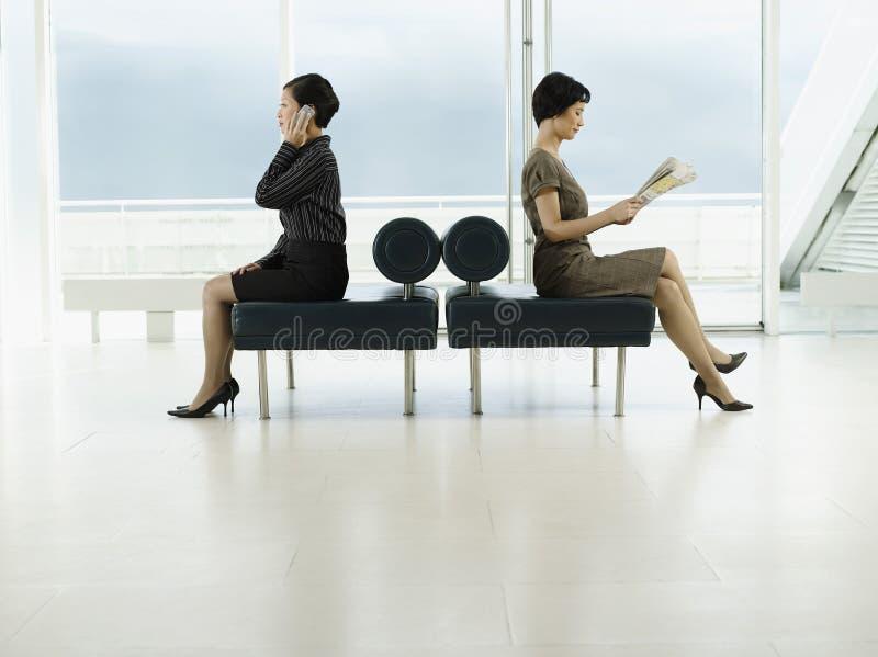 Femmes d'affaires avec le téléphone et le journal dans des directions opposées à image stock