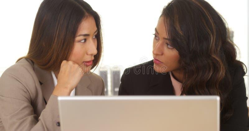 Femmes d'affaires de métis travaillant sur l'ordinateur portable image stock