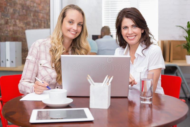 Femmes d'affaires de sourire collaborant avec l'ordinateur portable image stock