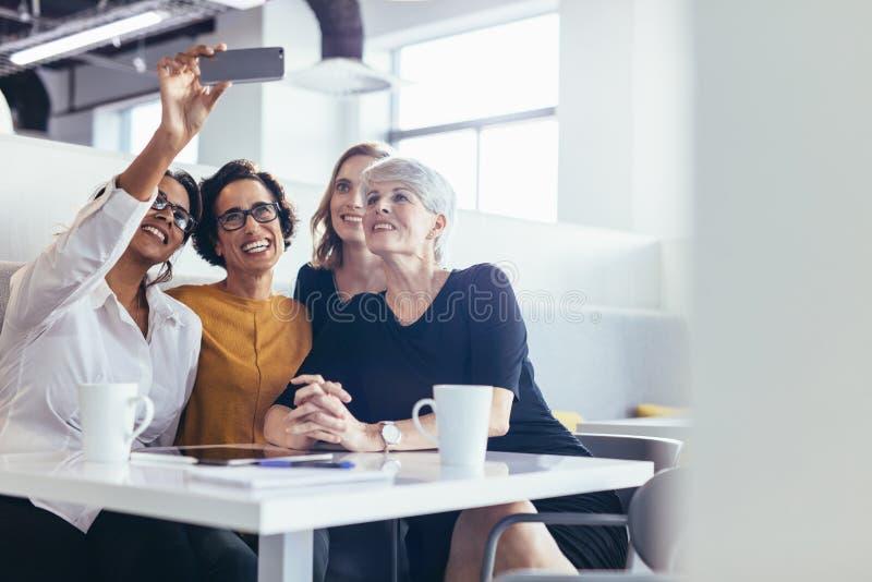 Femmes d'affaires prenant le selfie au cafétéria de bureau images libres de droits