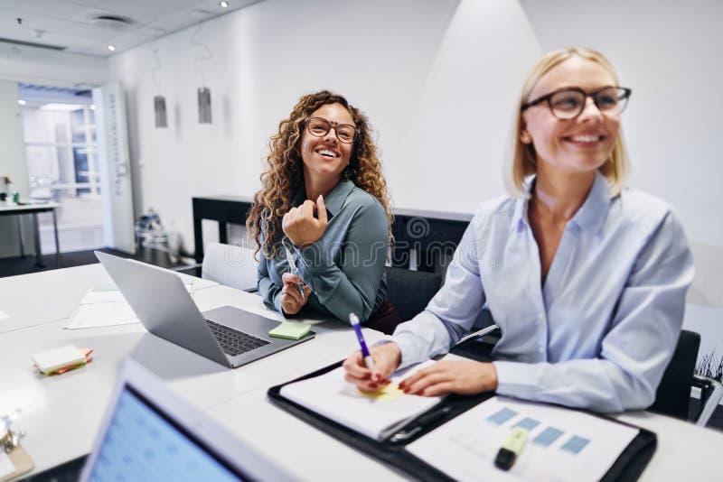 Femmes d'affaires riantes assises à une réunion de bureau photos stock