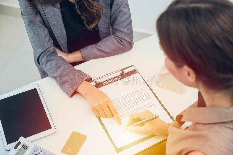 Femmes d'affaires s'occupant pour signer le contrat pour le prêt financier image stock