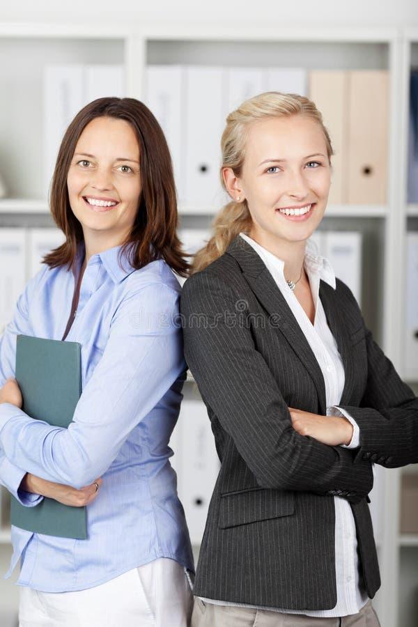Femmes d'affaires se tenant de nouveau au dos photographie stock libre de droits