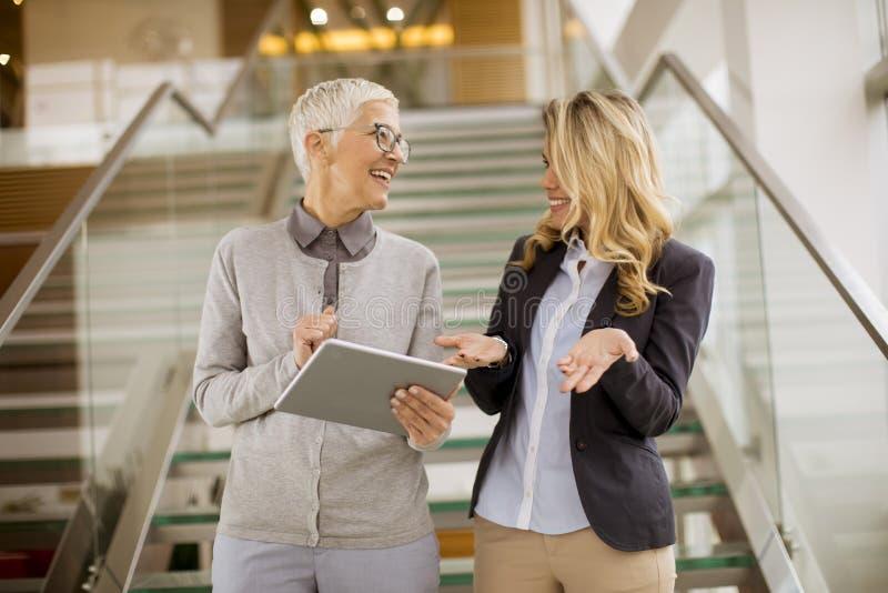 Femmes d'affaires supérieures et jeunes se tenant dans le bureau avec t numérique photos stock