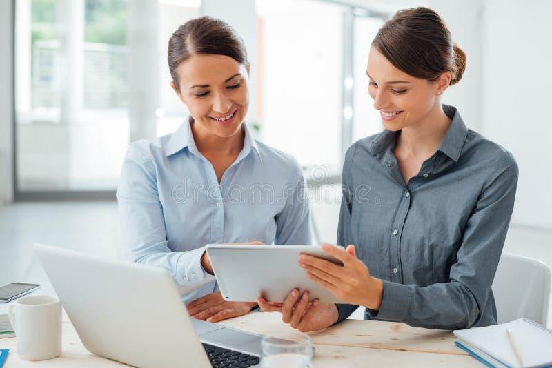 Femmes d'affaires travaillant ensemble sur un comprimé photographie stock libre de droits