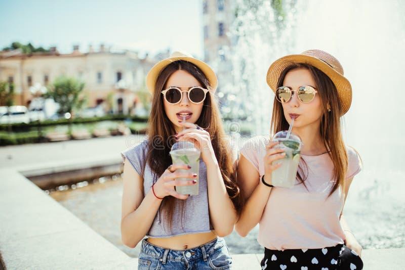 Femmes d'amis souriant buvant un cocktail dans la rue d'été image libre de droits