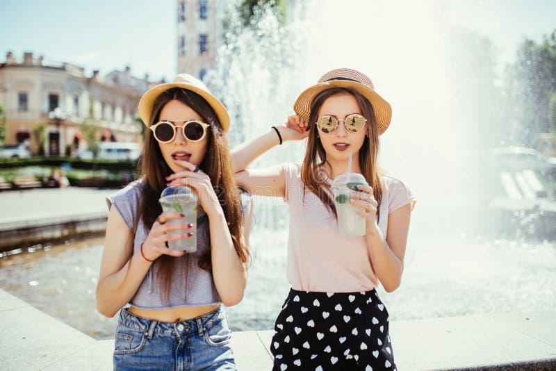 Femmes d'amis souriant buvant un cocktail dans la rue d'été photos libres de droits