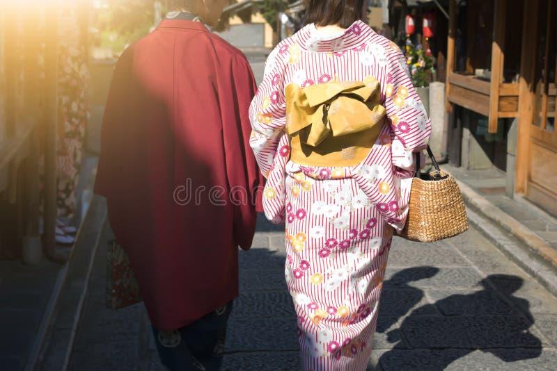 Femmes dans des kimonos japonais traditionnels marchant au temple avec le soleil photos libres de droits