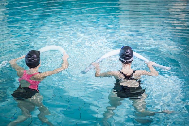 Femmes dans la piscine avec des rouleaux de mousse photo stock