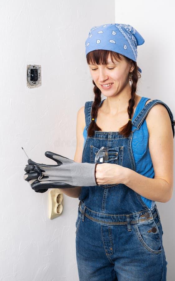 Femmes dans la profession masculine : Une fille répare un commutateur électrique avec un tournevis et des pinces images libres de droits