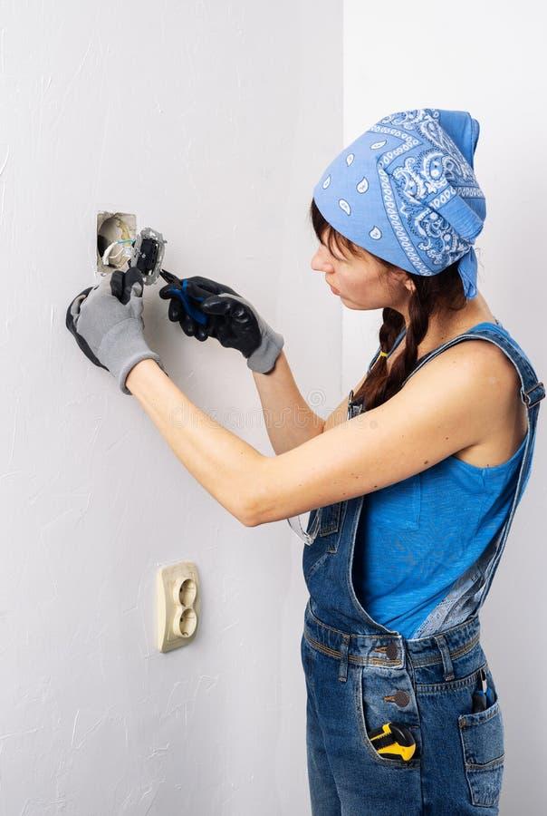 Femmes dans la profession masculine : Une fille répare un commutateur électrique avec un tournevis et des pinces photo stock