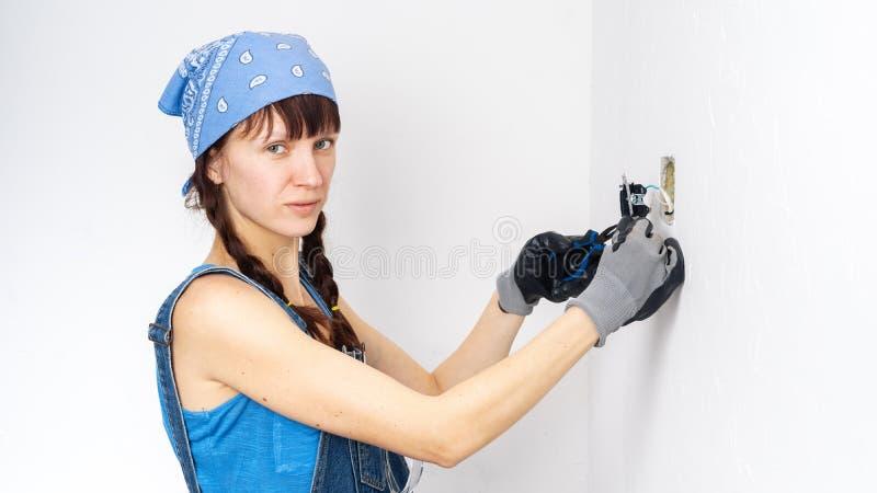 Femmes dans la profession masculine : Une fille r?pare un commutateur ?lectrique avec un tournevis et des pinces image libre de droits